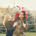 Happy soldier with family in park