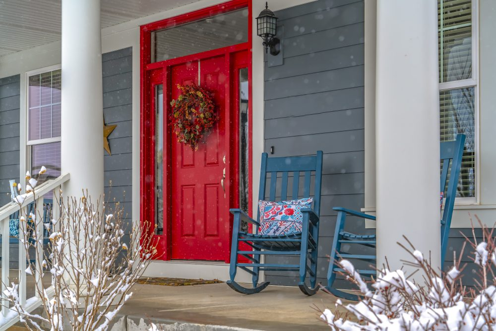 Winter view of home with red door and front porch